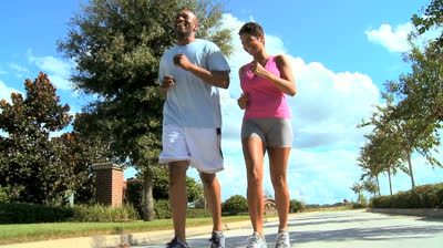 stock-footage-attractive-african-american-couple-jogging-on-suburban-roads-to-keep-fit