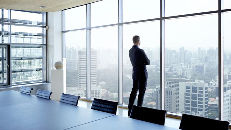Businessman looking out of window watching skyline